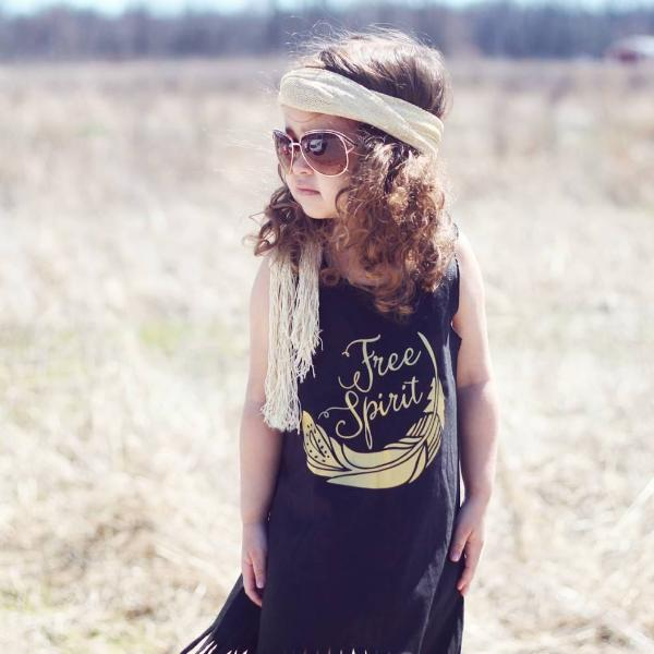 Little girl wearing black fringe dress with gold Free spirit writing and long boho headband