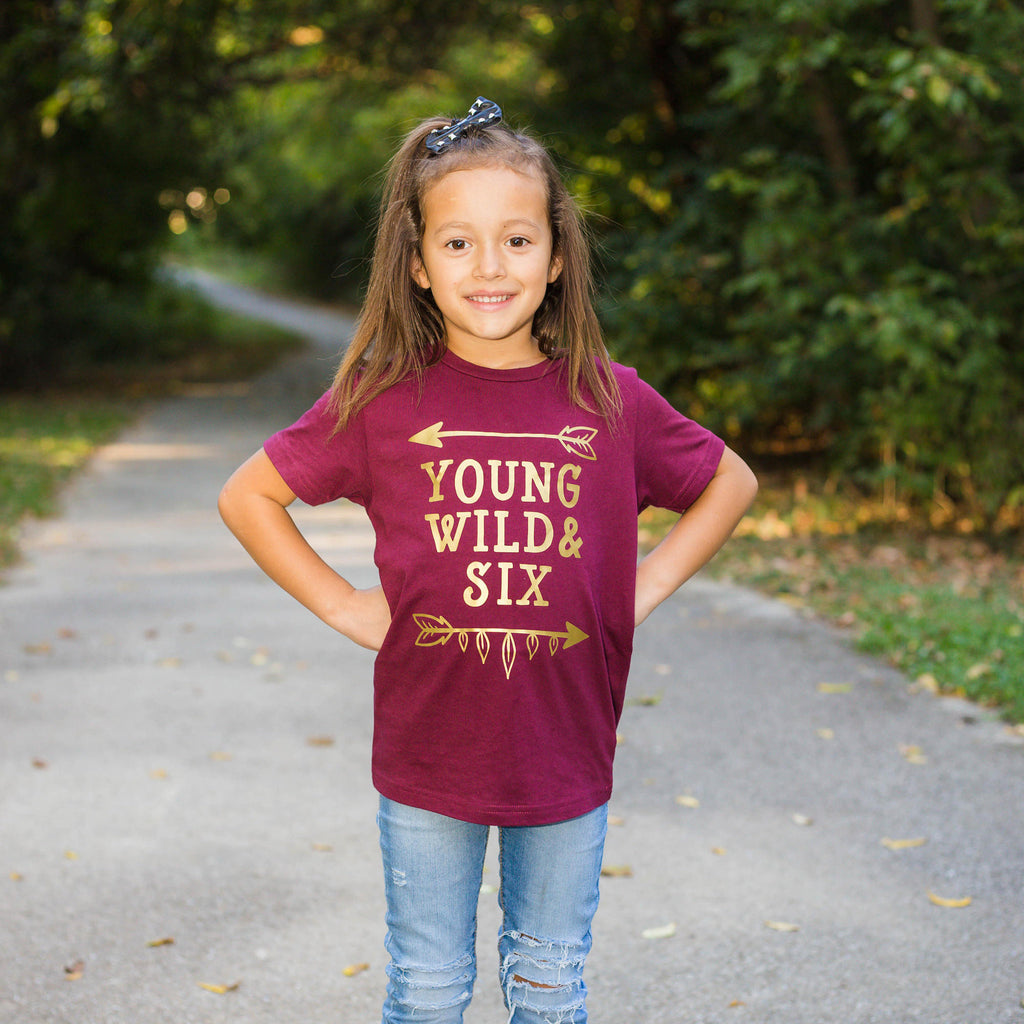 Little girl wearing maroon shirt with young wild and six in gold