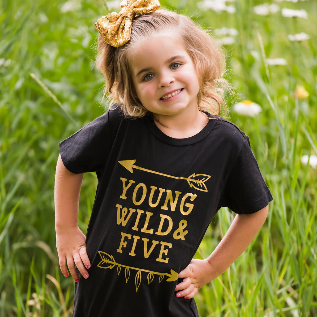Girl wearing black young wild and five t-shirt with gold writing in a field of flowers