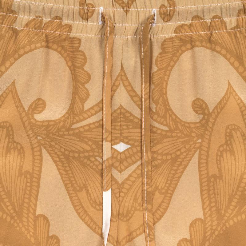 detail of a women silk pant in a yellow paisley print