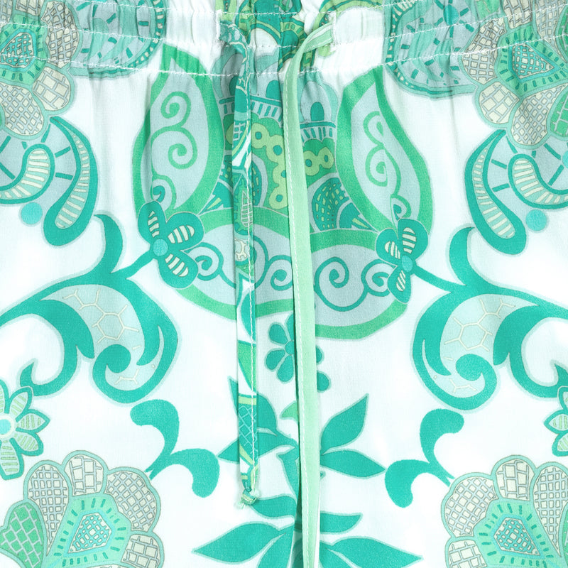 detail of a women silk pant in an emerald print