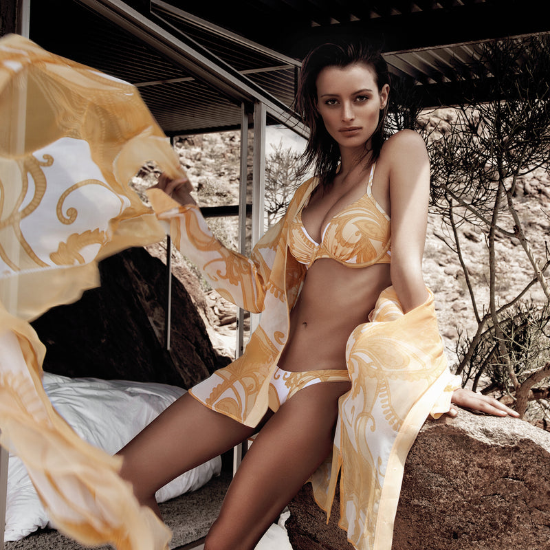 woman lounging in a yellow paisley print bikini and silk blouse