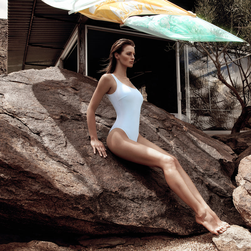 woman leaning against a rock wearing a classic one-piece swimsuit in pastel blue