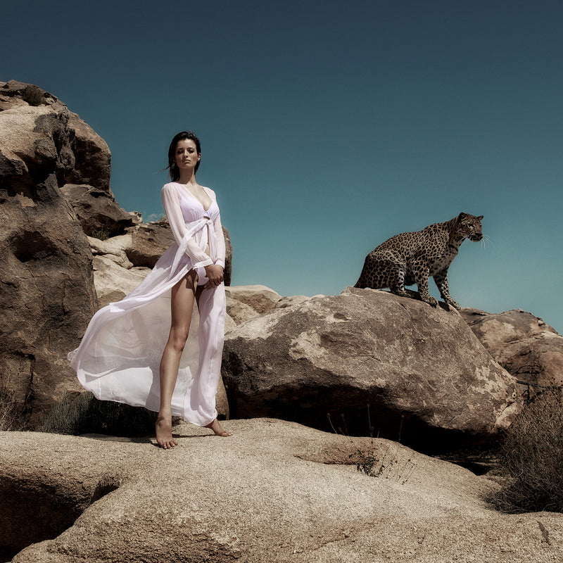 a cheetah and a woman in a lavender dress and bikini standing in the desert of palm springs