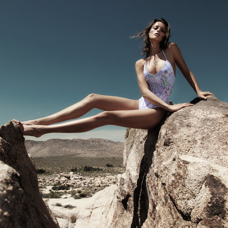 woman lounging in the desert of palm springs in a one-piece multicolor pastel swimsuit