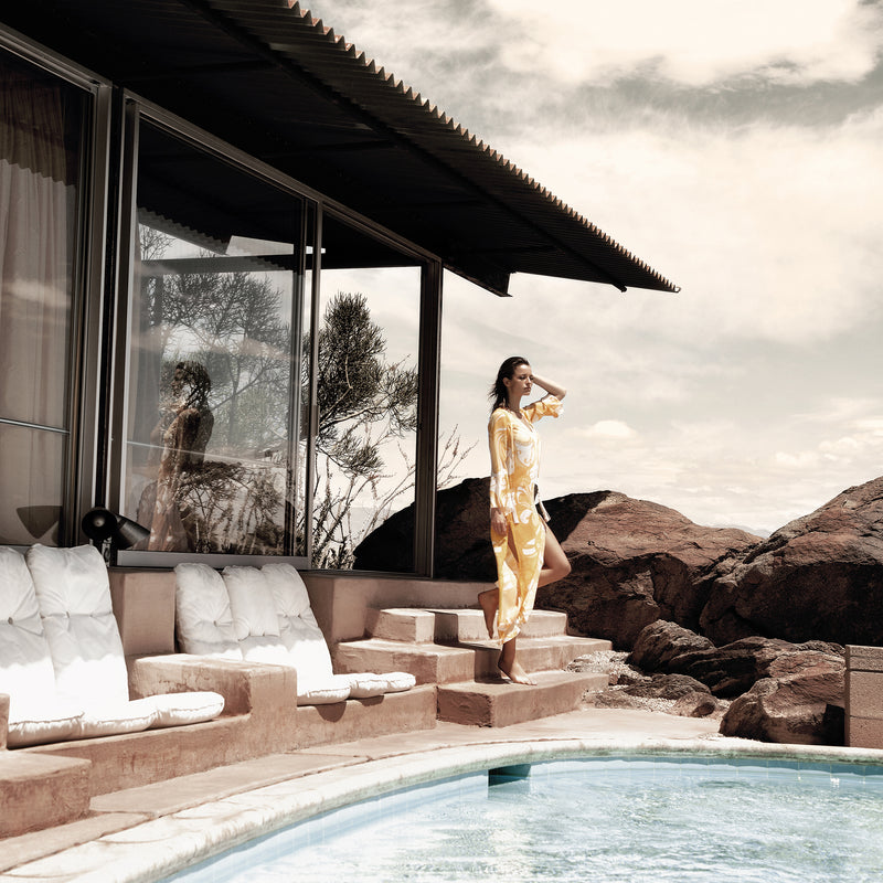 woman by a pool in palm springs wearing a silk kaftan in a yellow paisley print