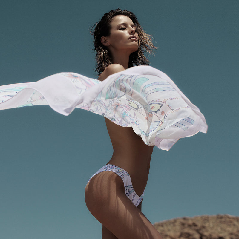 women wearing a bikini bottom and holding a multicolor pastel print silk pareo