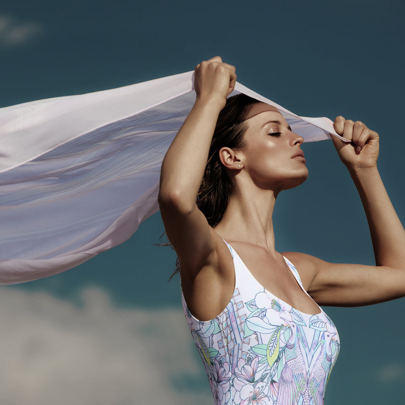 woman wearing a multicolor one-piece swimsuit and putting on a silk lavander bandana