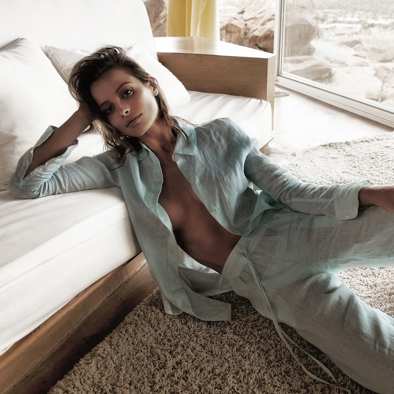 woman lounging with an assorted linen shirt and pant in pastel blue