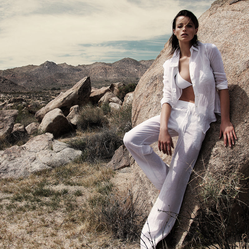 woman wearing a white bikini, linen shirt and pants in the desert of palm springs