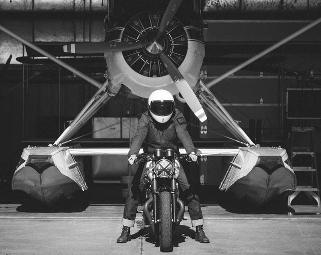 men on motorcycle in front of airplane