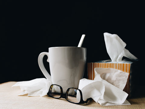 white ceramic mug on white table beside black eyeglasses and tissues