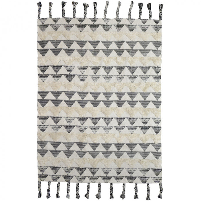 Rug with a combination of braids, tassels and looped details in neutral tones