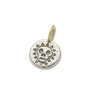 Silver round charm with skull carving