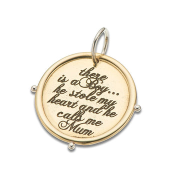 Round gold charm with silver bail and text