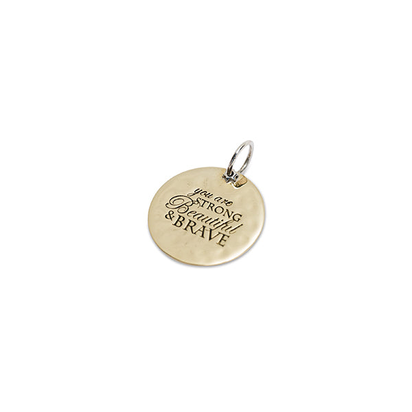 Round brass charm engraved with 'you are strong, beautiful & brave'
