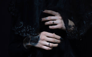 Alternative engagement rings with salt and pepper diamonds and skulls on two pale hands with a gothic black background with a black veil obscuring the ghostly model