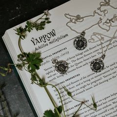 Yarrow  silver necklace, obol coin style with a green witch book background