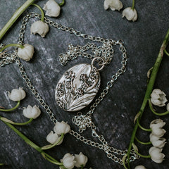 Lily of the valley flowers and a silver lily of the valley pendant