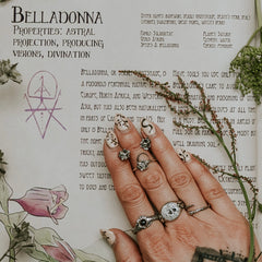 Belladonna jewellery with a green witch book about herbs