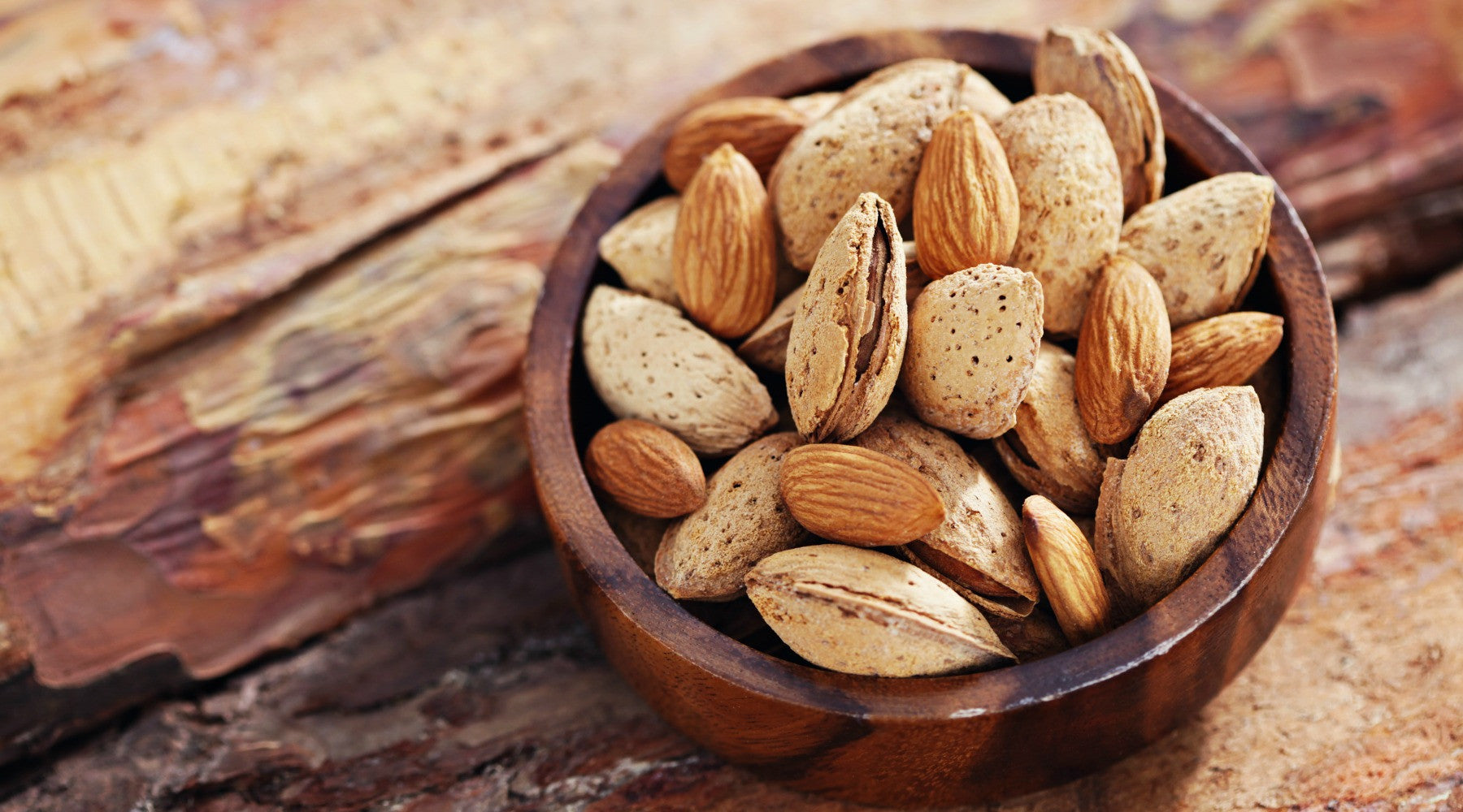 bowl of almonds on a rough board