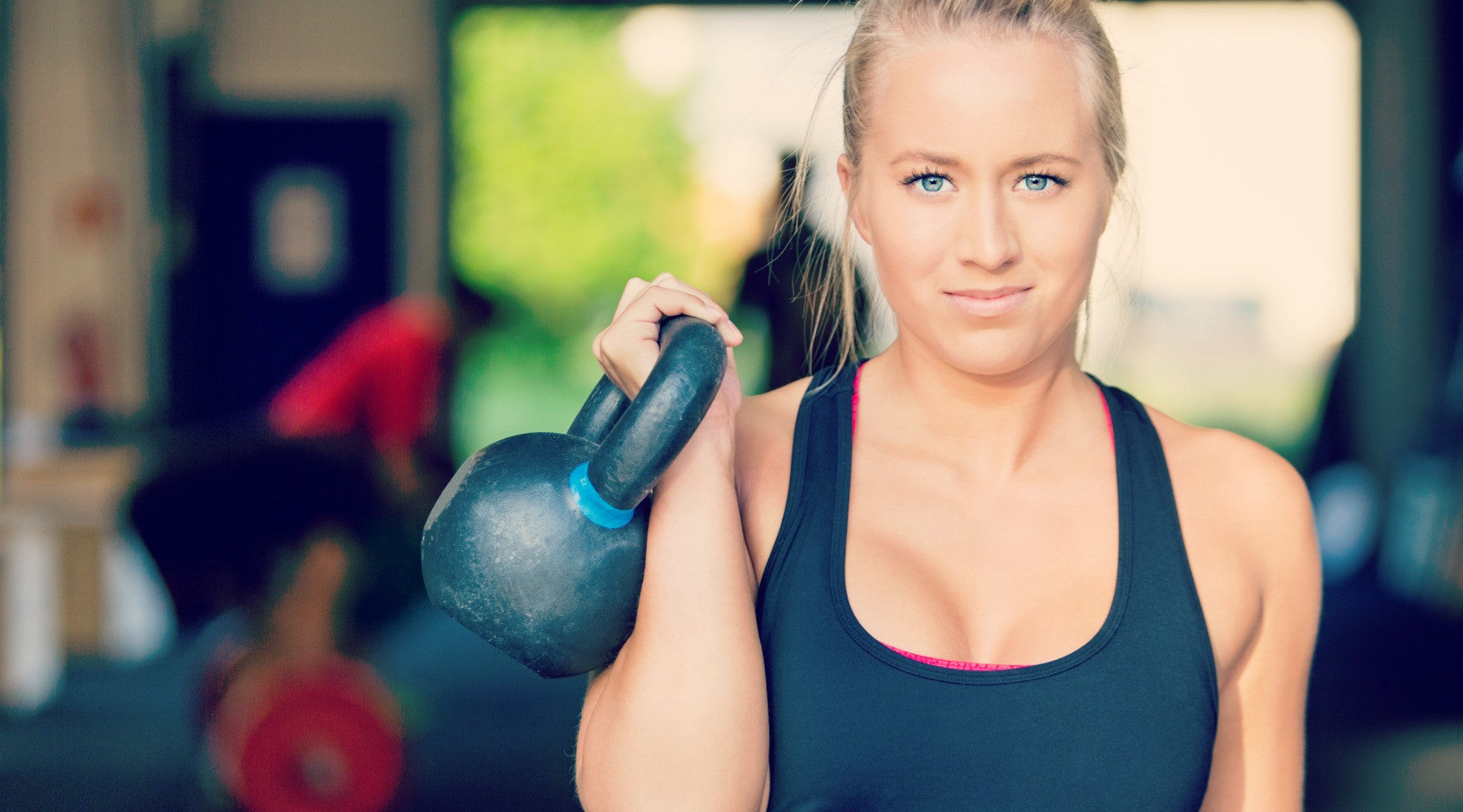 women in gym with kettlebell