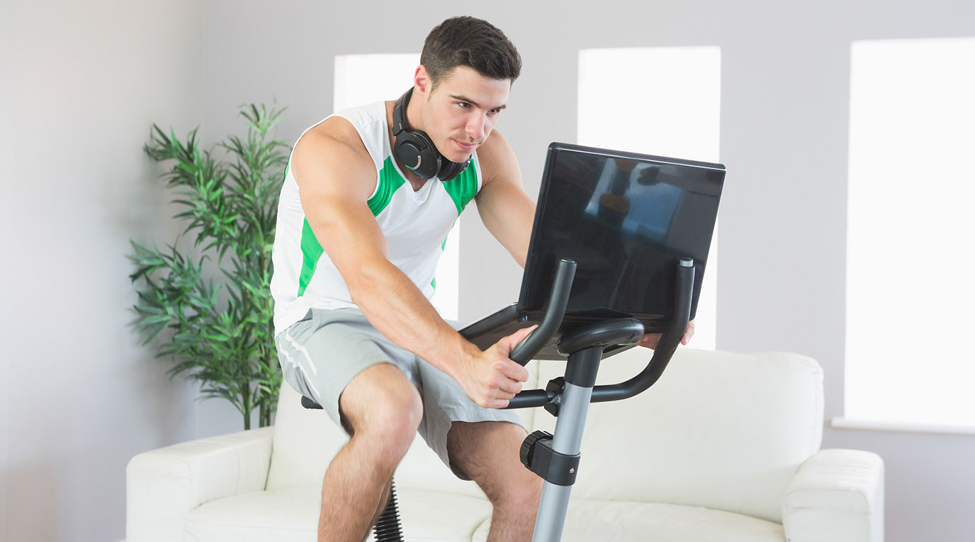 man on exercise bike working on laptop