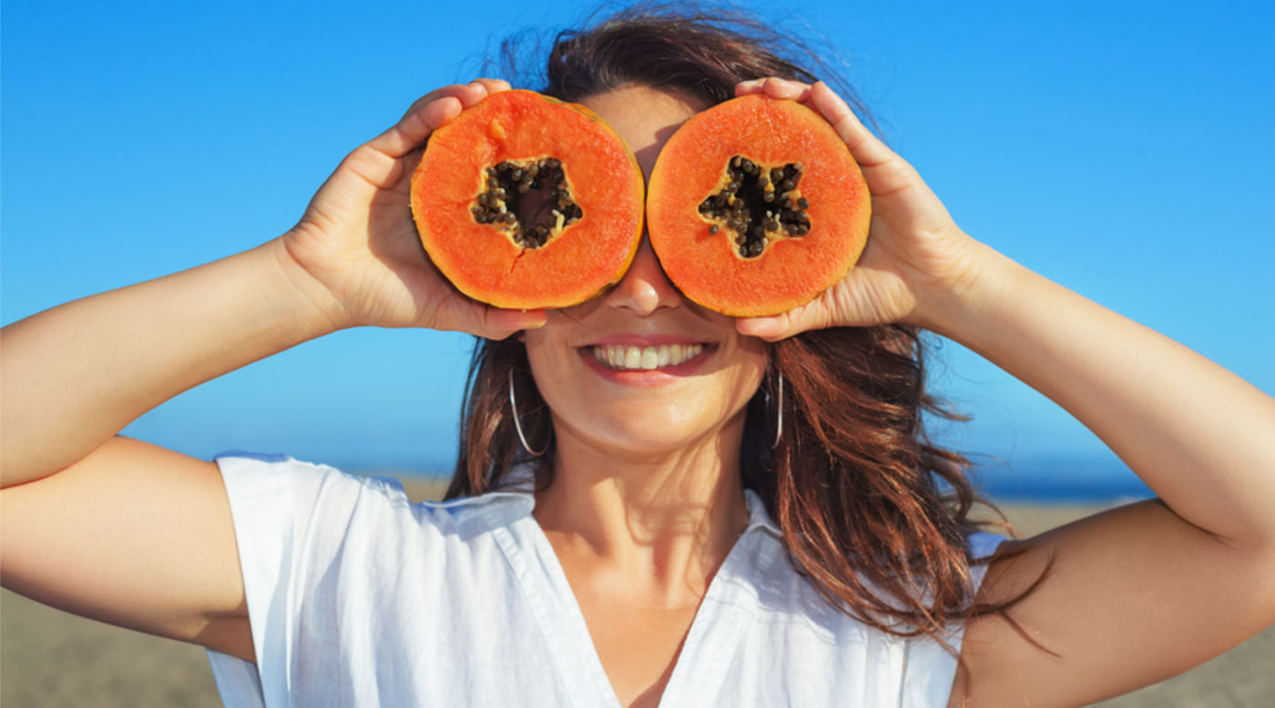 Woman using papaya slices as glasses