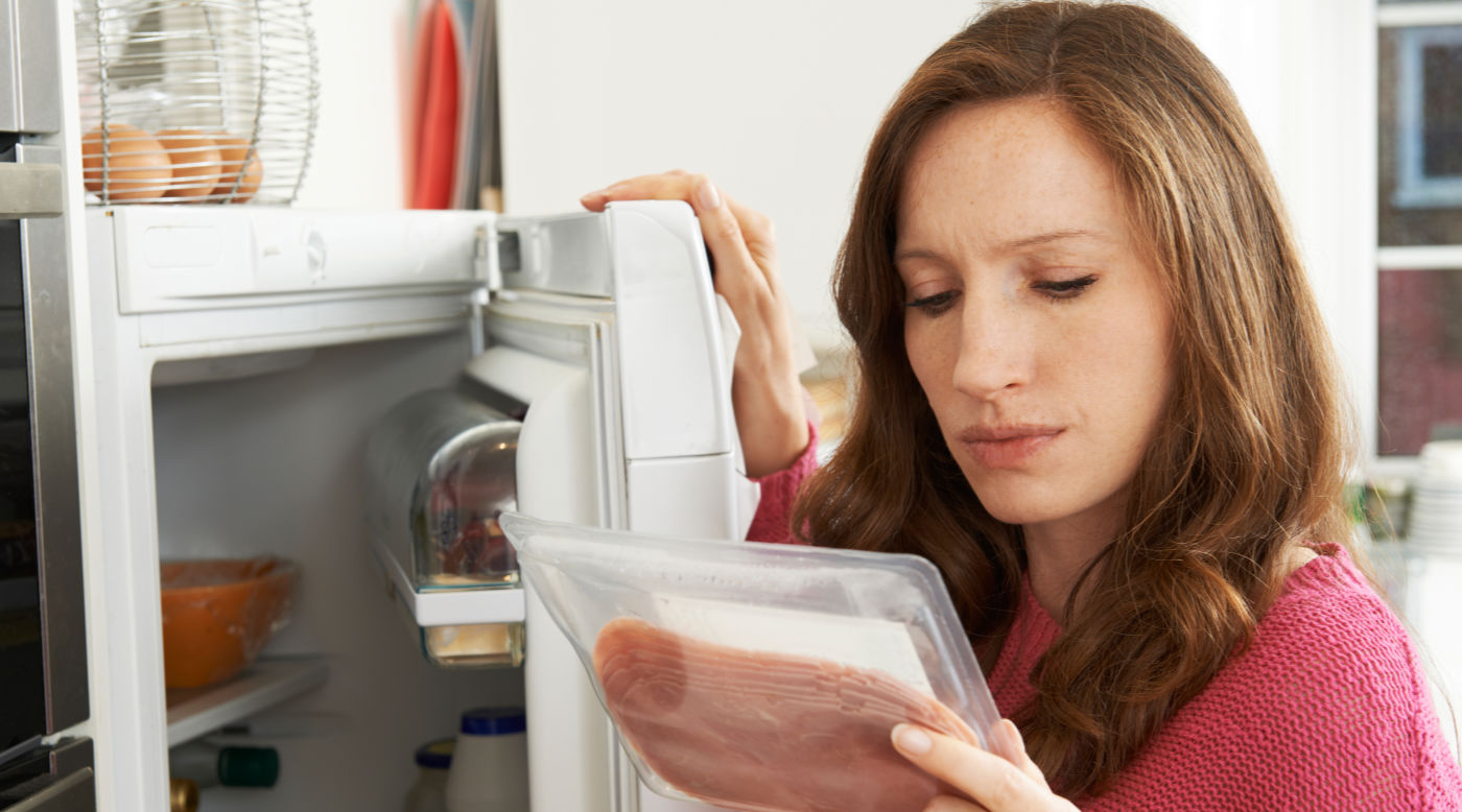 woman reading label on meat package