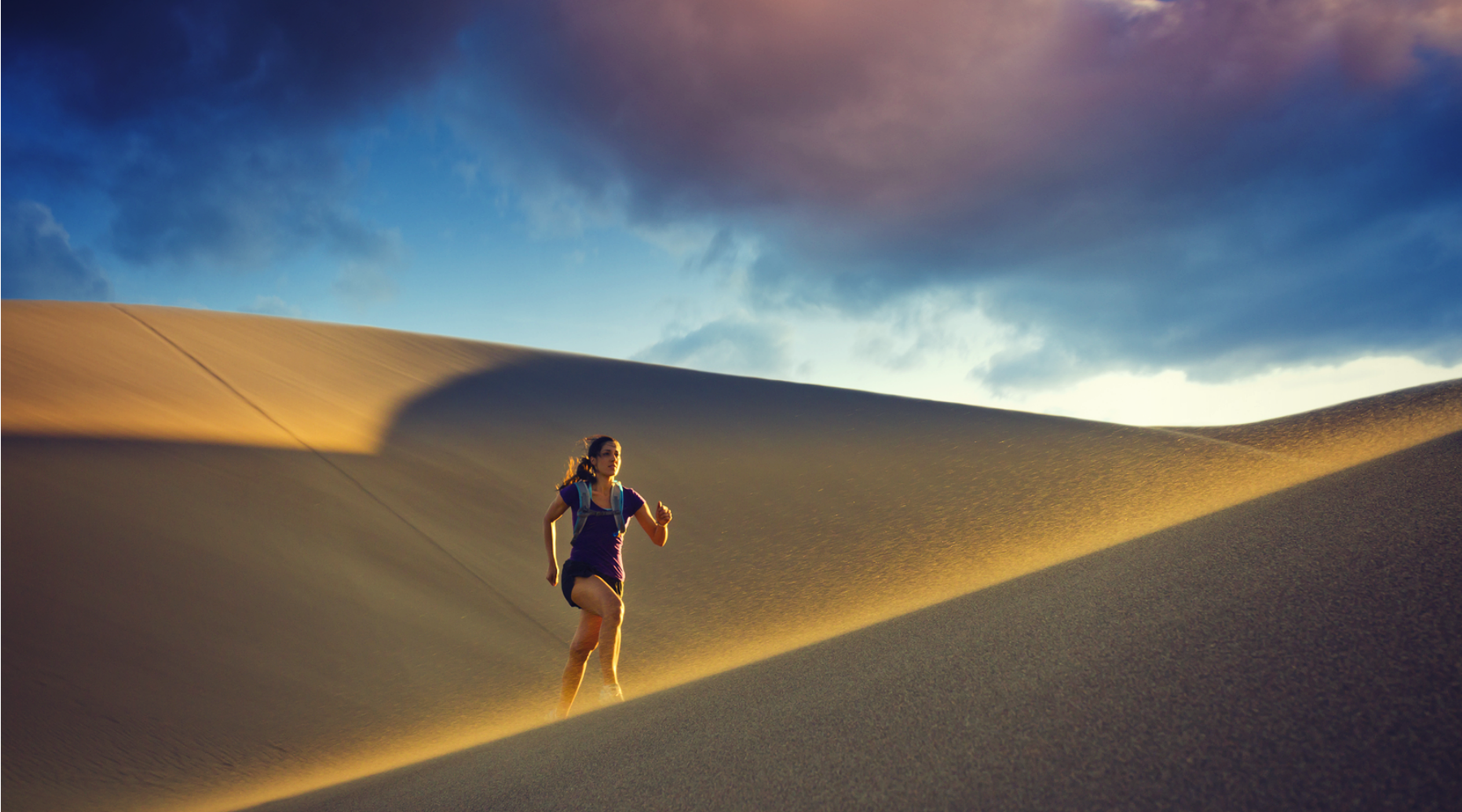 Woman running in sand dunes
