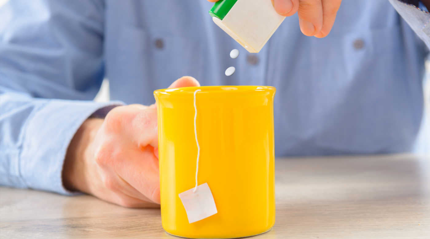 man adding artificial sweetener to tea