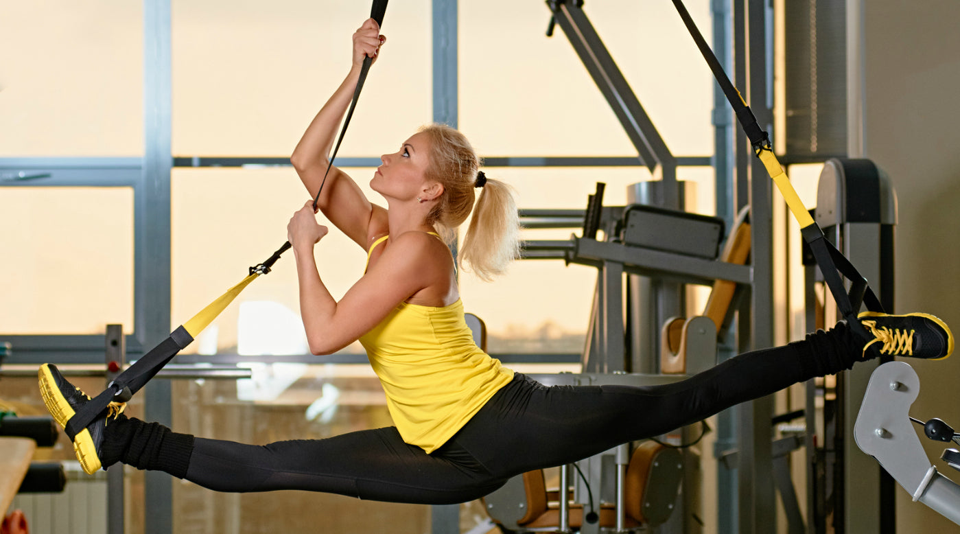 Woman doing splits on trx