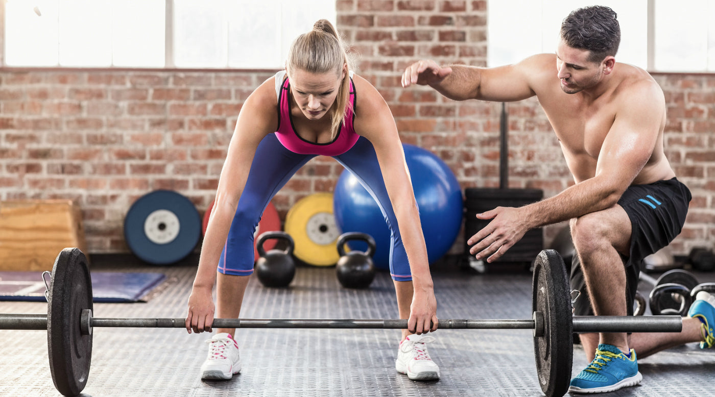 woman with trainer in cross fit gym