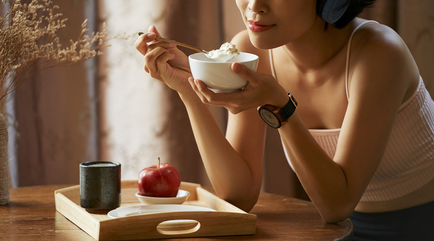 woman eating breakfast thoughtfully