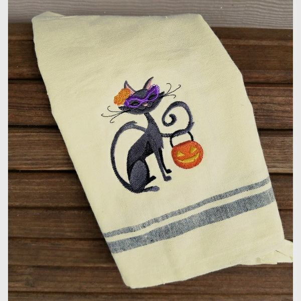 Fancy Halloween cat towel holding pumpkin.