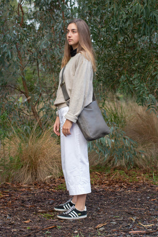Model wears Ripple and Co Leather Jude Petite Cross Shoulder Bag Elephant Grey