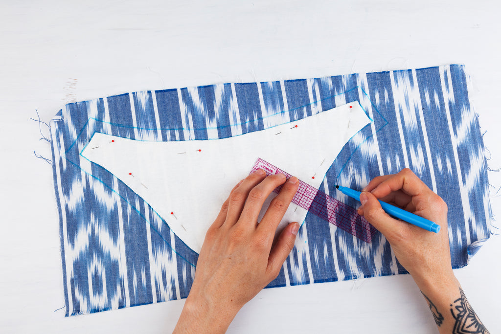 white sleeve pattern piece pinned onto blue patterned fabric, hands tracing around