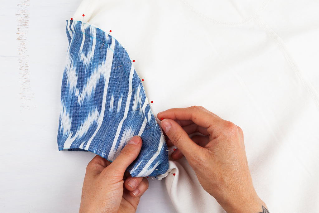 hands pinning a patterned sleeve onto a white top