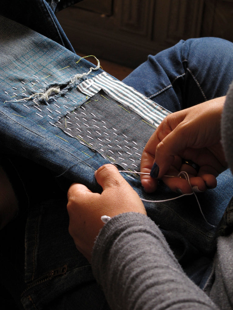 person mending a pair of jeans