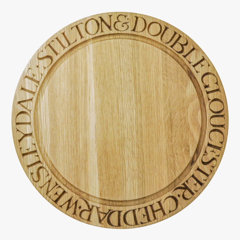 "Emma Bridgewater Wooden Circular Cheese Board - A round cheese board made of oakwood in Thailand. Decorated with carved letterings spelling ""CHEDDAR, WENSLEYDALE, STILTON & DOUBLE GLOUCESTER"". A great vintage touch to your kitchen."