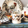 "Emma Bridgewater cream earthenware mug with hen and chicken decorations on the outside. Black lettering on the inside spells ""Wake Up Rise And Shine"". Part of the Hen & Toast hand crafted collection."