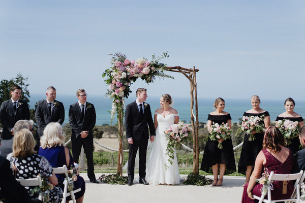 A lush floral and wooden arch framed Gemma's wedding. Photo by All My Wednesdays.