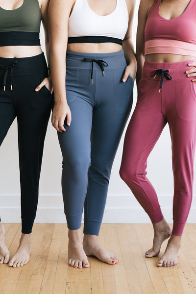 Three women standing wearing the Warm up Joggers in black, dusty blue and mauve
