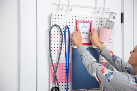 woman hanging a frame on the wall