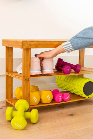 hand getting a shoe from a shoe rack with lifting bells