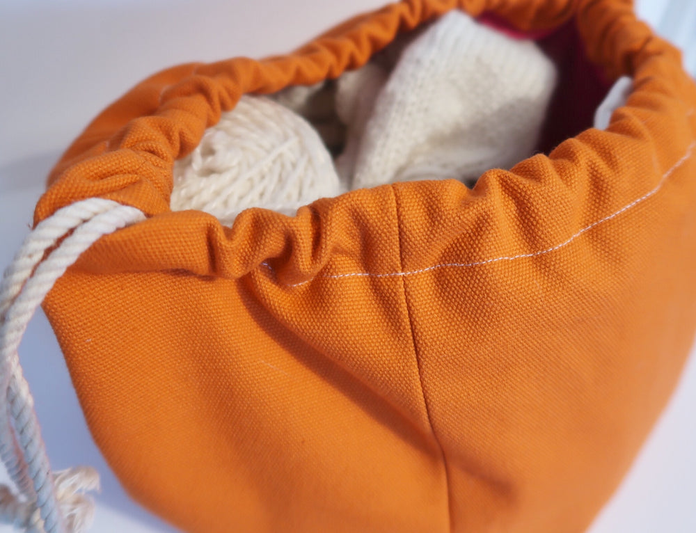 Canvas Cube Knitting Project Bag in Orange Colour, large size for sweaters and granny blankets. Cube shaped drawstring bag shown with drawstring pulled to close bag