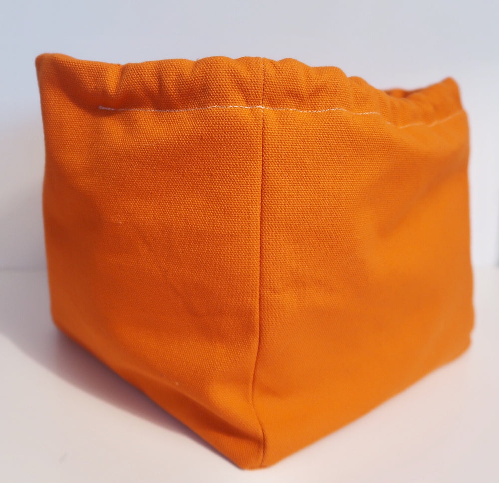 Canvas Cube Knitting Project Bag in Orange Colour, large size for sweaters and granny blankets. Cube shaped drawstring bag shown side on and standing upright
