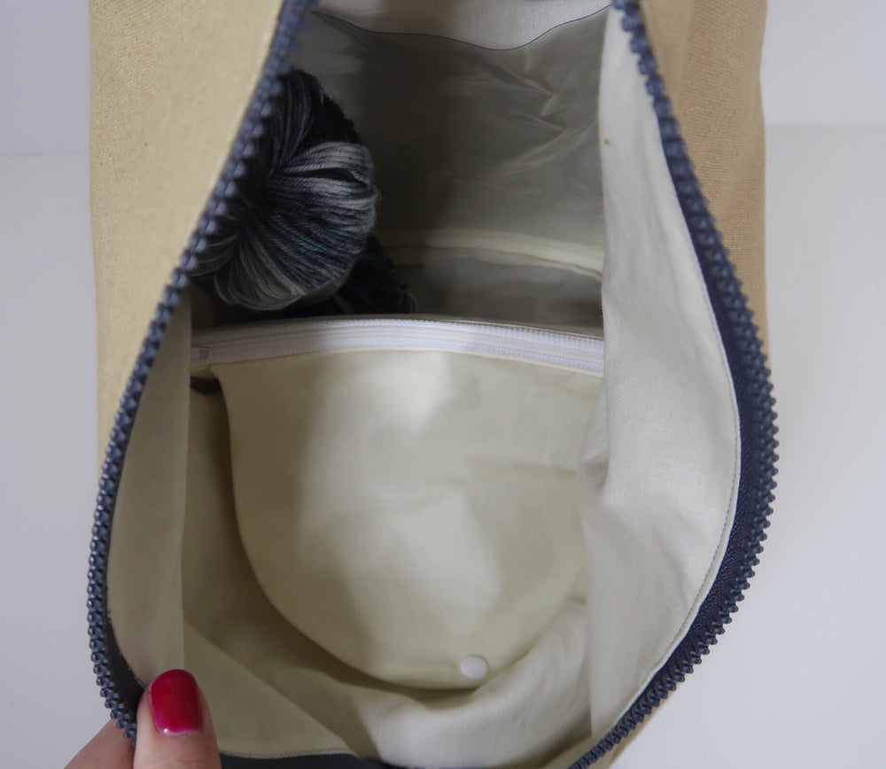 Knitting Project Bag ~ Knitters Carry All Backpack, inside view of the bag with zip open and showing the features of notions pouch, clear pocket, poppers for lining opening and stitch marker holder with yarn inside the project bag area and the panel closed. Shown in Biscuit