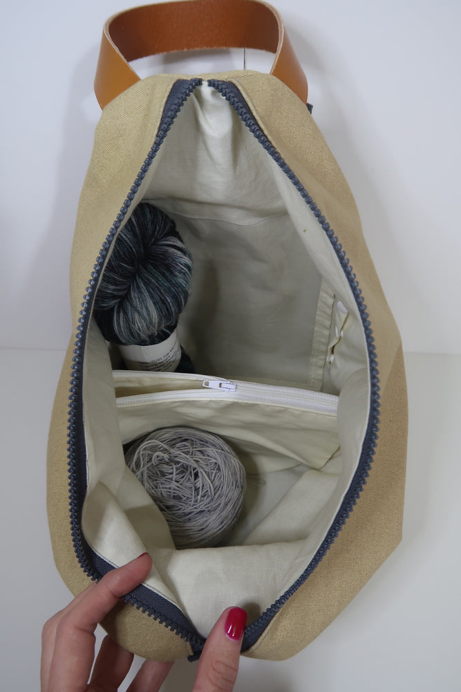 Knitting Project Bag ~ Knitters Carry All Backpack, inside view of the bag with zip open and showing the features of notions pouch, clear pocket, poppers for lining opening and stitch marker holder with yarn inside the bag and shown in Biscuit
