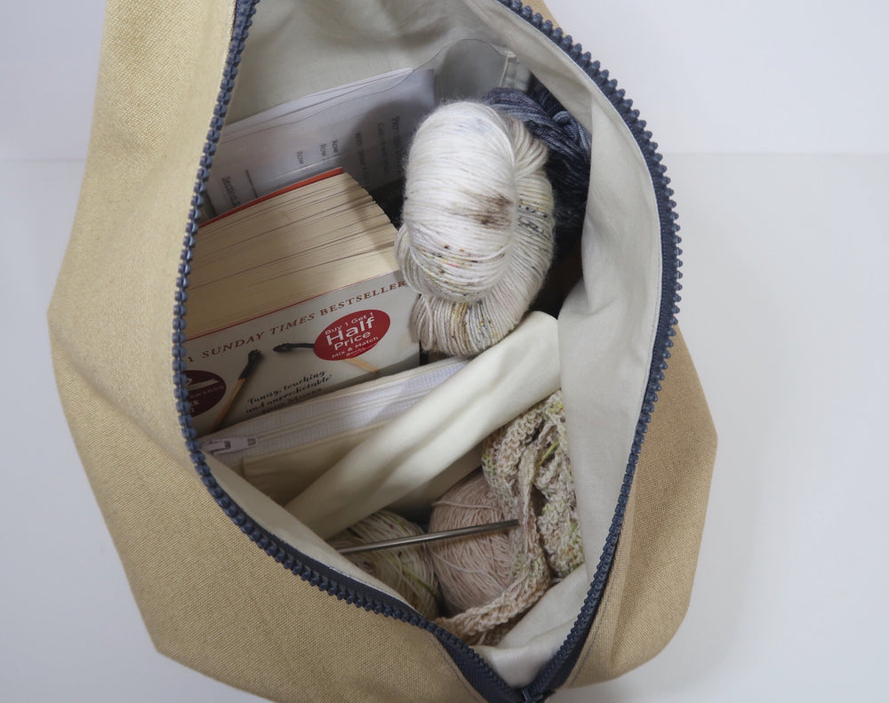 Knitting Project Bag ~ Knitters Carry All Backpack, inside view of the bag with zip open and showing the features of notions pouch, clear pocket, poppers for lining opening and stitch marker holder with yarn, knitting project and book inside the bag. Shown in Biscuit